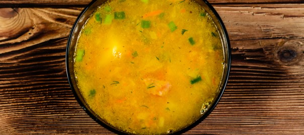 Vegetable soup in a glass bowl on wooden table. Top view